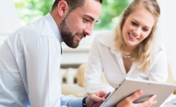 Business woman and man in work meeting looking at presentation on tablet computer